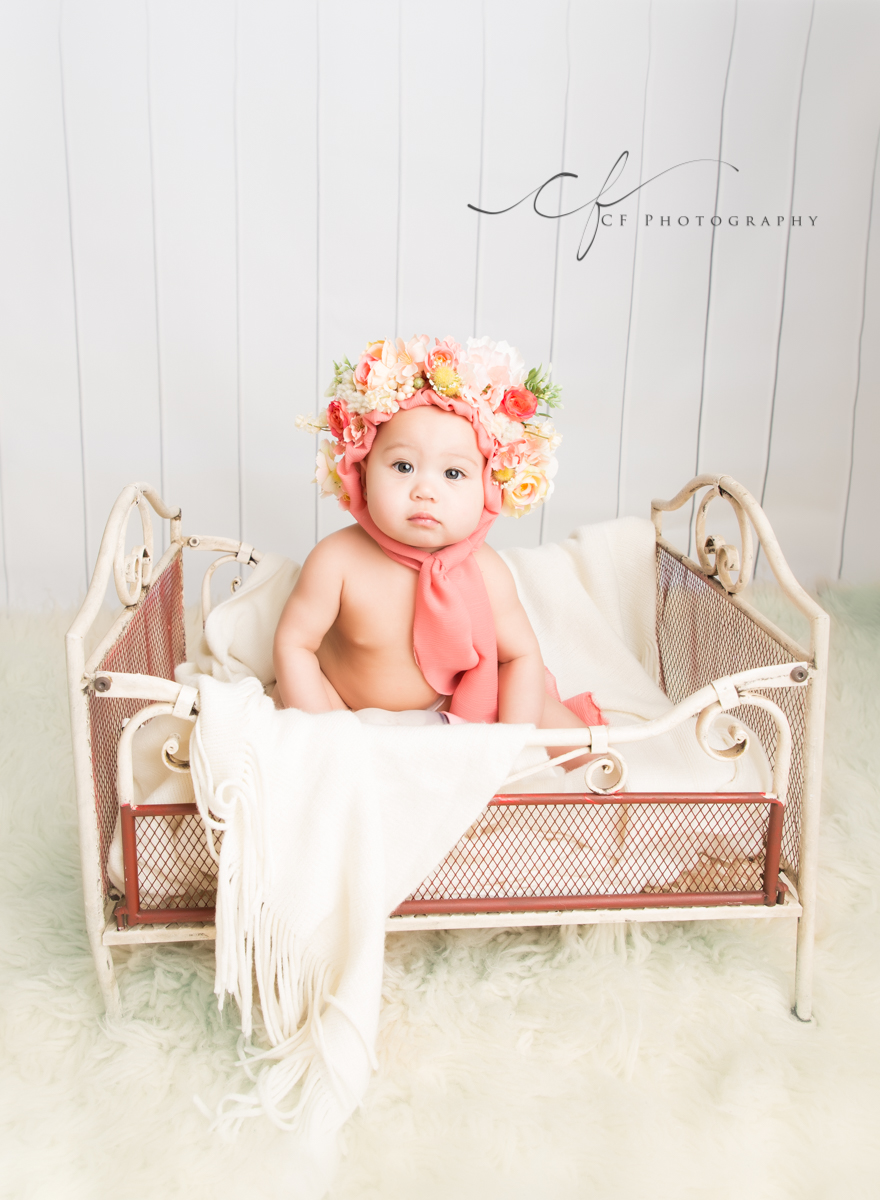 6 month baby wearing pink floral bonnet in rustic white metal bed