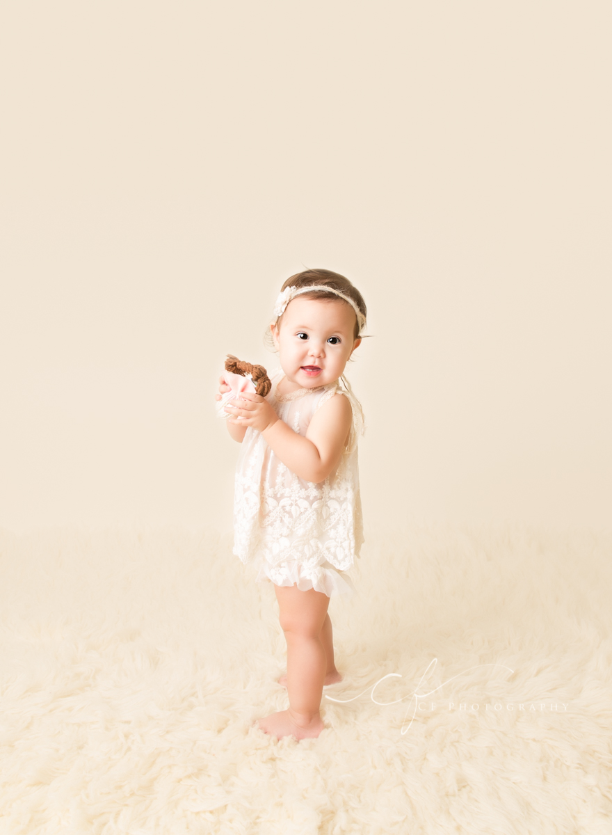 One year old Olivia wearing cream heirloom top and bloomers holding knit doll standing on cream flokati with cream backdrop