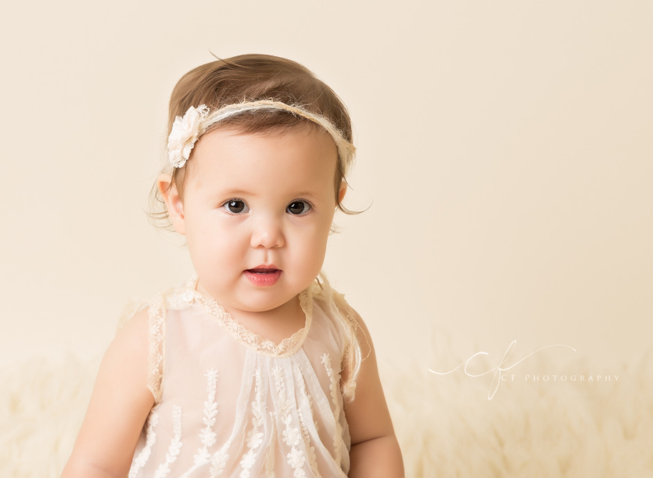 one year old girl portrait with cream bow tieback and heirloom top
