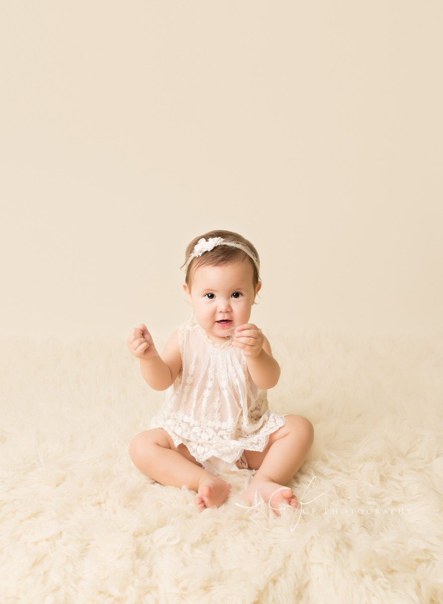 one year old girl sitting on cream flokati with cream backdrop wearing heirloom top and bloomers